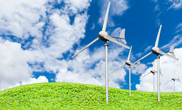Eco power, wind turbines generating electricity. Against partly cloudy blue sky background and grassland, green earth concept royalty free stock photos