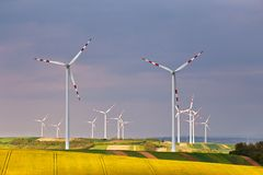 Eco power. Wind turbines generating electricity. Green environment. Spring sunny day on green field with wind power generators in Austria Stock Photography