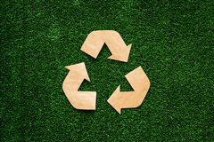 Eco recycle sign made of craft paper on green grass background top view copy space royalty free stock photos
