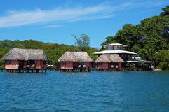 Eco resort with thatched bungalow over water Stock Images