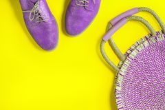 Eco round straw bag and purple shoes on vibrant yellow. Round rattan straw bag and purple shoes on vibrant glowing trendy yellow background. Top view with copy royalty free stock image