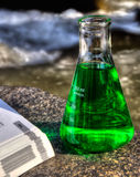 Eco Science. A laboratory flask and a text book beside a mountain stream suggesting eco science.  This is an HDR image Stock Image