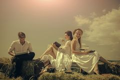 Eco-settlement. Happy women or girls reading books on bench. Man typing on vintage typewriter on hay Stock Photo