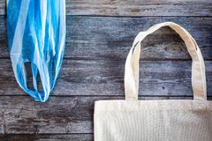 Eco Shopping Bag against a plastic bag on wooden background, Flat Lay. Save planet earth stock image