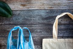 Eco Shopping Bag against a plastic bag on wooden background, Flat Lay. Save planet earth royalty free stock images