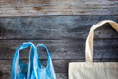 Eco Shopping Bag against a plastic bag on wooden background, Flat Lay. Save planet earth royalty free stock photo