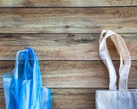 Eco Shopping Bag against a plastic bag on wooden background, Flat Lay. Save planet earth. Eco Shopping Bag against a plastic bag on wooden background, Flat Lay stock photography