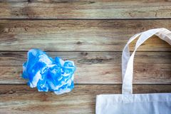 Eco Shopping Bag against a plastic bag on wooden background, Flat Lay. Save planet earth stock photo