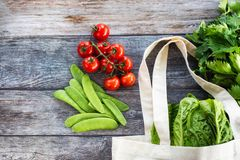 Eco Shopping Bag with fresh organic vegetables and salad on wooden background, Flat Lay stock photography