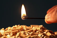 Eco solution. Closeup on wood pellet with start fire flame royalty free stock images