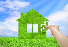 Eco stwarza ognisko domowe pojęcie, ręki budowy zielony dom od łamigłówki Obraz Royalty Free