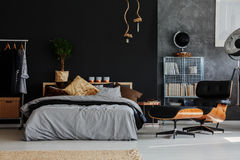Eco style bedroom. Eco style grey and black bedroom with comfortable bed and armchair royalty free stock images