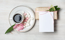 Eco style gift box and greeting card with pink flowers and coffee cup a over the wooden background. Top view, flat lay Stock Images