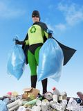 Eco superhero. Holding two plastic bags full of domestic trash standing on garbage heap - waste segregation concept Royalty Free Stock Photo