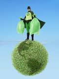 Eco superhero and garbage free planet. Eco superhero holding two plastic bags full of garbage standing on green Earth planet - clean environment concept Royalty Free Stock Image