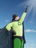 Eco superhero looking towards the Sun. With his hand raised up and pointing the same direction Stock Photo