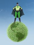 Eco superhero and green planet. Eco superhero standing on green Earth planet - clean environment concept Royalty Free Stock Image