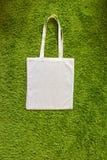 Eco-Tasche gemacht von unbemalter Baumwolle 100 auf einem grünen künstlichen Grashintergrund Beschneidungspfad eingeschlossen Mod Stockfotos