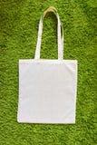 Eco-Tasche gemacht von unbemalter Baumwolle 100 auf einem grünen künstlichen Grashintergrund Beschneidungspfad eingeschlossen Mod Stockfotografie