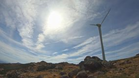 Eco Theme, wind turbine, detailed on top of mountain. Vegetation and granite stones, sky with some clouds as background stock footage