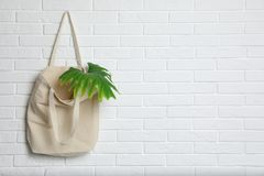 Free Eco Tote Bag With Leaf Hanging On White Brick Wall. Royalty Free Stock Photos - 138318738