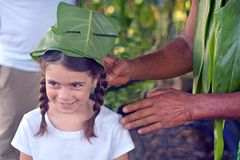 Eco tourism in Rarotonga Cook Islands. Cook Islander Pa men age 75 prepares a hat made out of a tree leaf to a tourist girl age 08 during an Eco tourism tour in royalty free stock photos