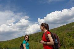 Eco-Tourismus und gesundes Lebensstilkonzept Junges Wanderermädchen mit dem Rucksack, der unter den Wolken steht Stockbilder