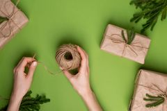 Eco twine in hands and gifts with green plants in craft paper on green background stock images
