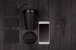 Eco vänlig kaffemall för design som annonserar och brännmärker - svart pappers- kopp, telefon för tom skärm, etikett, kort, lock, royaltyfria foton