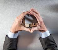 Eco-vänskapsmatchen byggnadsskydd med affärsmannen räcker att omfamna ett hus Royaltyfri Fotografi