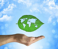 Eco world. Opened hand holding a green leaf with world map inside on a blue sky background. Eco world concept Royalty Free Stock Photos