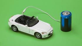 Ecobilen som drivas av batterier på grön bakgrund Arkivbilder