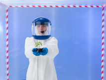 Ecofriendly. Close-up of female biologist wearind white protection suit and blue mask holding plant seedling in her hands, inside a room surrounded with red and royalty free stock photos