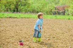 Ecologia e prote??o ambiental crian?a pequena que planta uma flor Dia de terra solos e adubos Explora??o agr?cola do ver?o imagens de stock