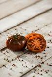 Ecologic black Tomato. On the wood table Royalty Free Stock Photos