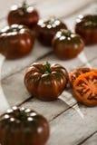 Ecologic black Tomato. Group Ecologic black Tomato on the wood table, slice tomato Royalty Free Stock Images