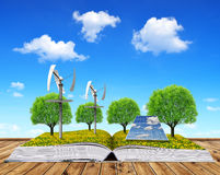 Ecological book with solar panel and wind turbines. Stock Photos