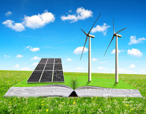 Ecological book with solar panel and wind turbines on meadow. Royalty Free Stock Image