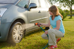 Ecological car wash. Woman washing her car in garden without detergents in ecological way Stock Image