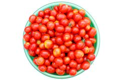 Ecological cherry tomatoes in a basin. Fresh ecological red cherry tomatoes in a round basin isolated on white background Royalty Free Stock Image