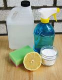 Ecological cleaning. Vinager bottle, spray bottle, sponge, bowl with bicarbonate de soda and half on a lemon Stock Image