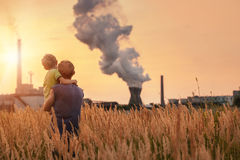Ecological concept image. Father with son looking on chemical plant emissions at sunset time Royalty Free Stock Images