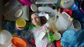 Ecological concept, the threat of plastic pollution. The girl lies in a pile of multi-colored plastic. Garbage falls on. Her, she cries stock video