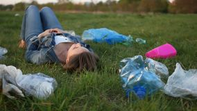 Ecological disaster, plastic pollution of the planet. A woman is lying on the grass in the middle of plastic garbage and. Staring at the sky stock video