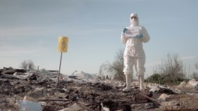 Ecological disaster, woman in protective suit and mask holding poster with stop pollution slogan at landfill near sign. Ecological disaster, woman in protective stock video footage