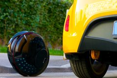 Ecological electric unicycle transport compare to gasoline diesel car stock images