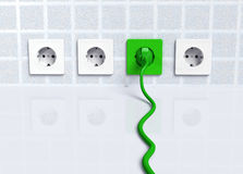 Ecological green plug into a socket Royalty Free Stock Image