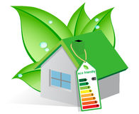 Ecological house. With a solar panel on the roof and wrapped in leaves with dew drops Royalty Free Stock Image