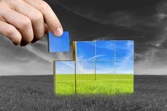 Ecological or positive concept. Male hand placing last piece of a cube of color grass field. Ecological or positive concept Stock Photos