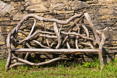 Ecological Table. An ecological bench made from tree branches on a grass field against a stone wall royalty free stock photos
